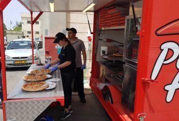 צוות המפעילים מגישים פיצות ממשאית מזון של פיצה האט